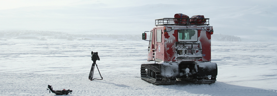 A pisten-bully, which is the preferred mode of transportation on the sea ice and the ice shelf around McMurdo station, at the foot of Mount Erebus. In the foreground is an easy-rig, a contraption used by director of photography Sylvestre Guidi to carry the camera.
